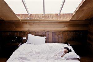 Kobieta leży przykryta kołdrą