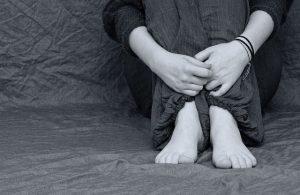 kobieta trzyma się za nogi