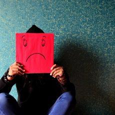 Czlowiek trzymający smutną maskę